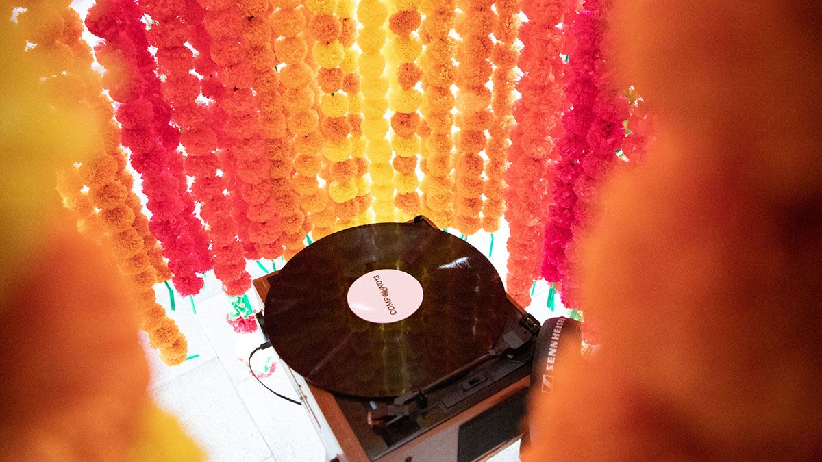 A record player sits inside a cylinder made from strings of flowers.