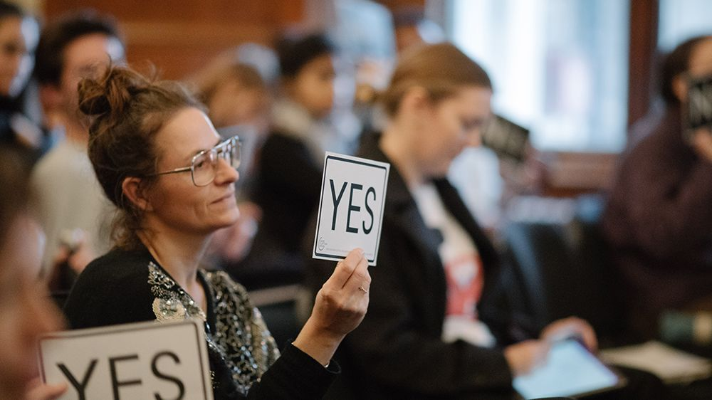 A woman holds a card that says 'yes'