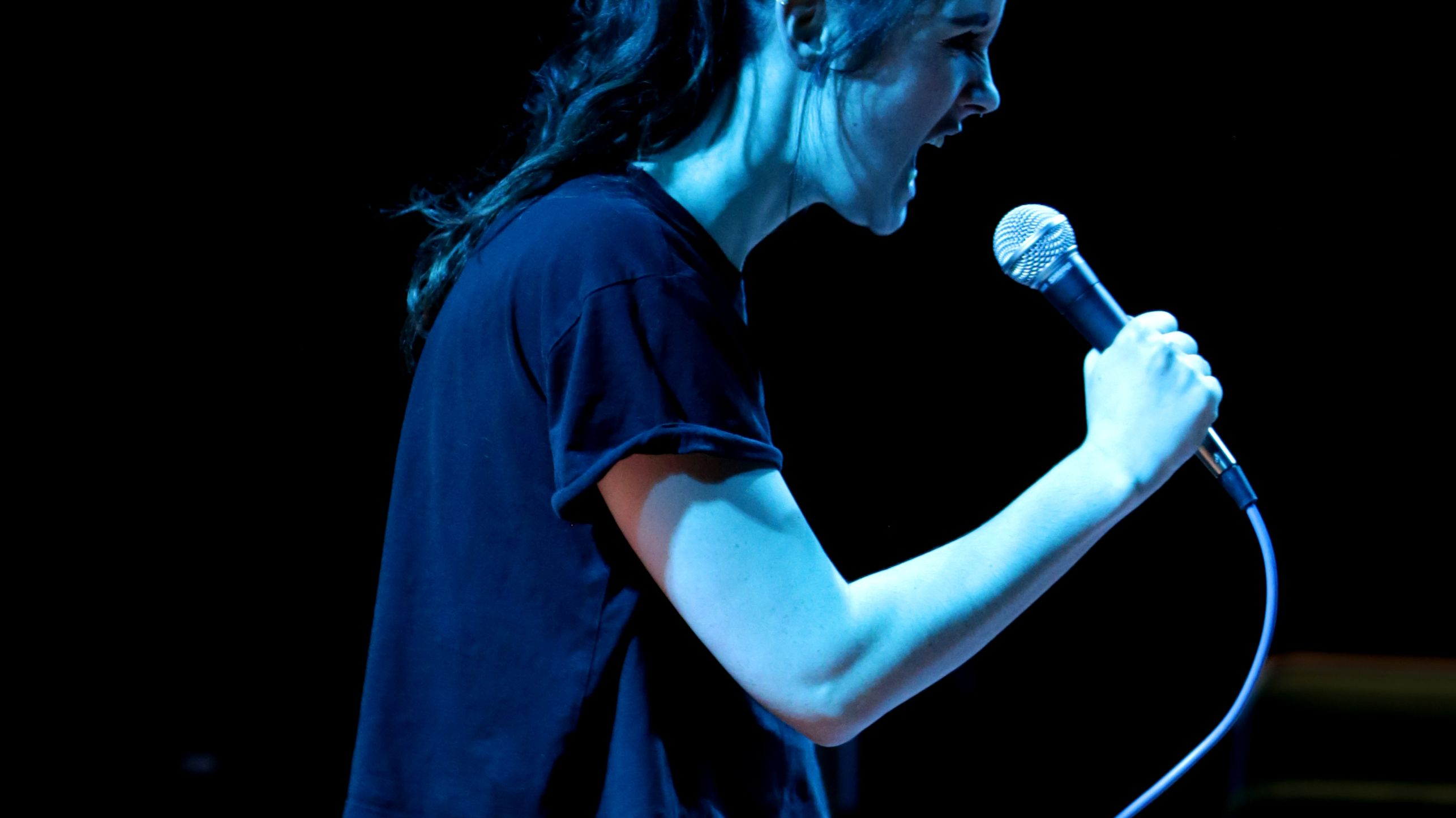 Girl in black t-shirt and jeans with a mic on stage.