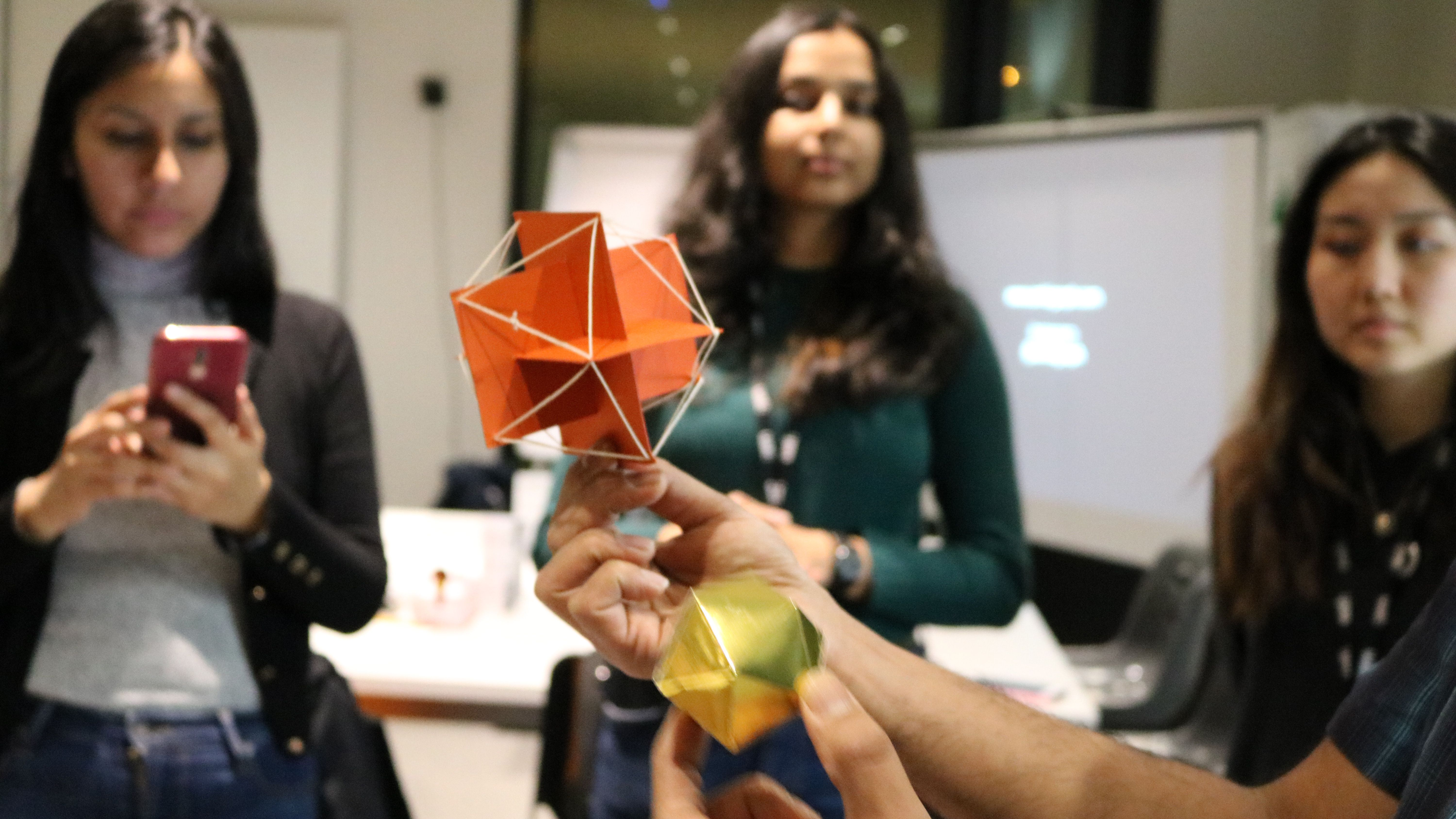 students watching an origami making demonstration