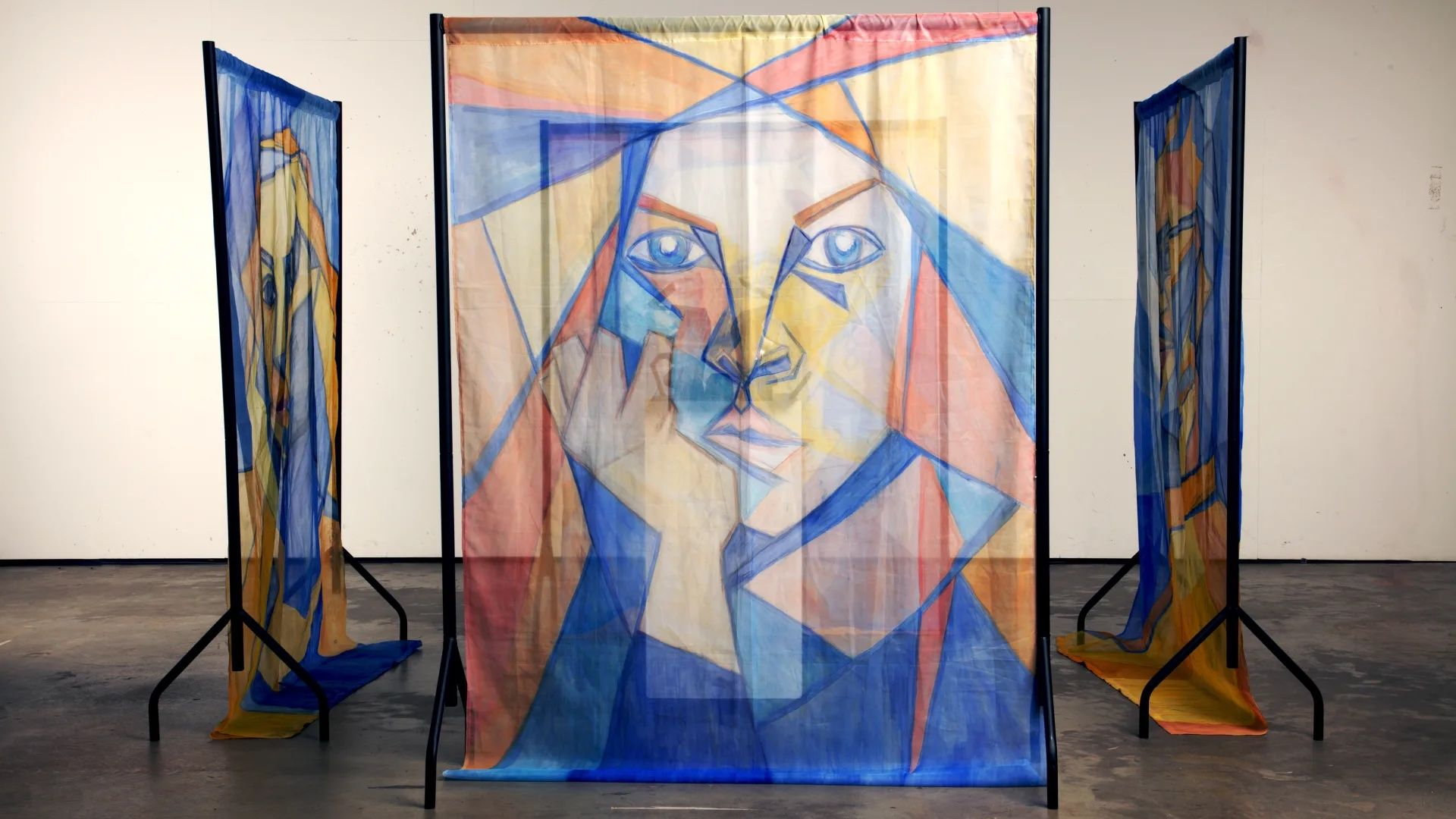 Three oil portraits on voile panels hung from steel sculpture