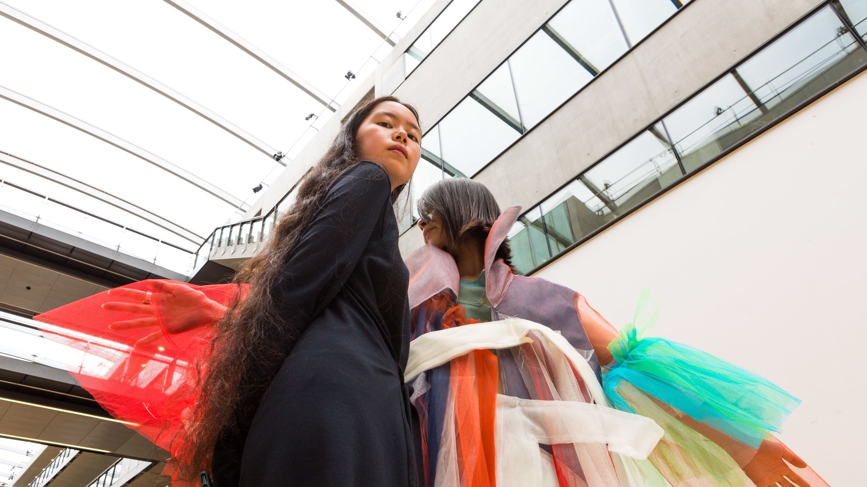 Vivian Li in black dress next to model wearing her colourful garment