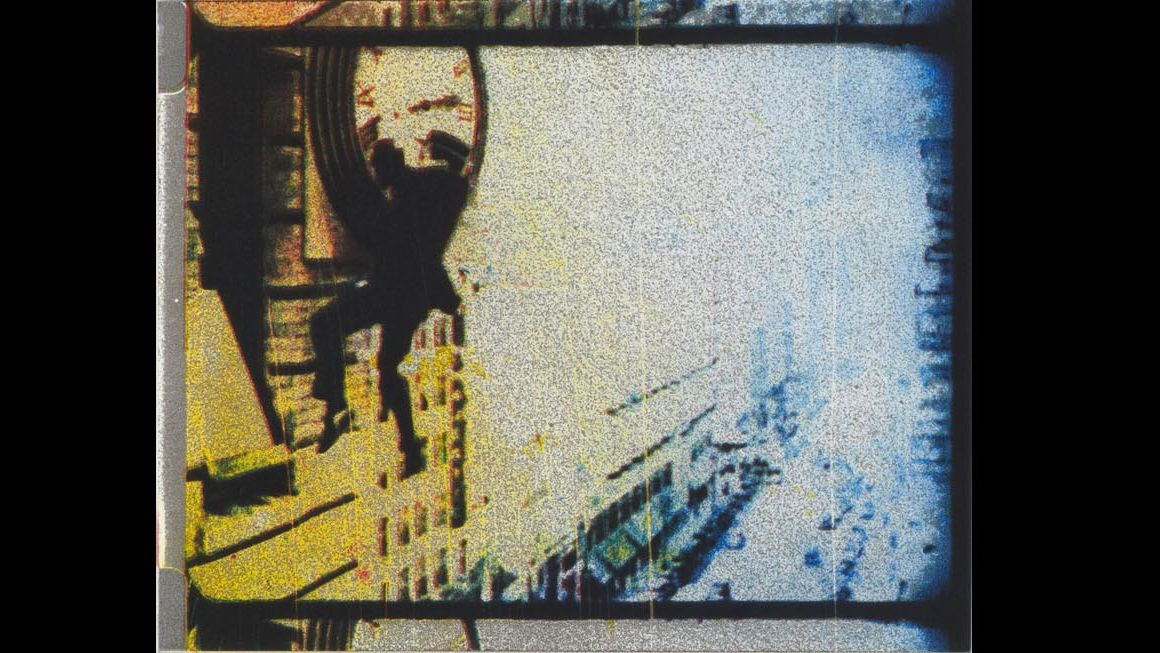 A yellow and blue negative of a man hanging from a clock