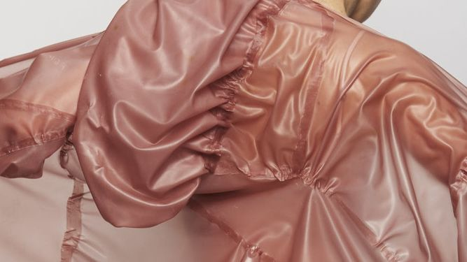 Close up of a light pink semi transparent, glossy suit