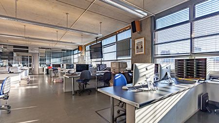 Sun streams into the newsroom, a room filled with desks and workstations.