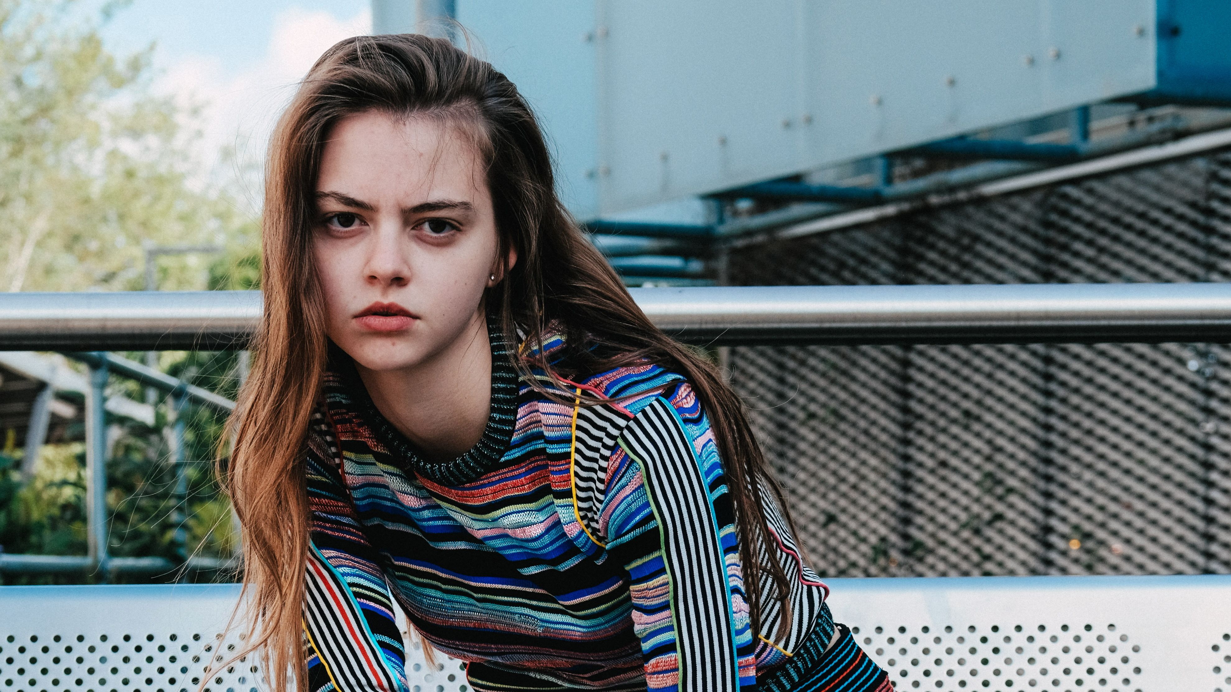 Model wearing garment made of colourful stripey knitted textiles by Priscilla Luong.