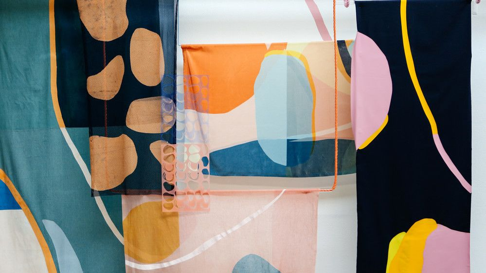 A collection of patterned textiles featuring organic shapes in blues, blacks, pinks and oranges.