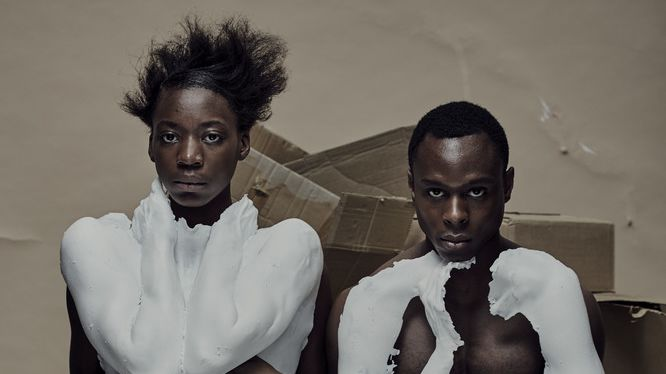 Two black models sitting on cardboard boxes with parts of their body covered in plaster cast.