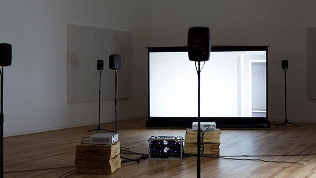 A gallery space with four speakers and a projection screen set up