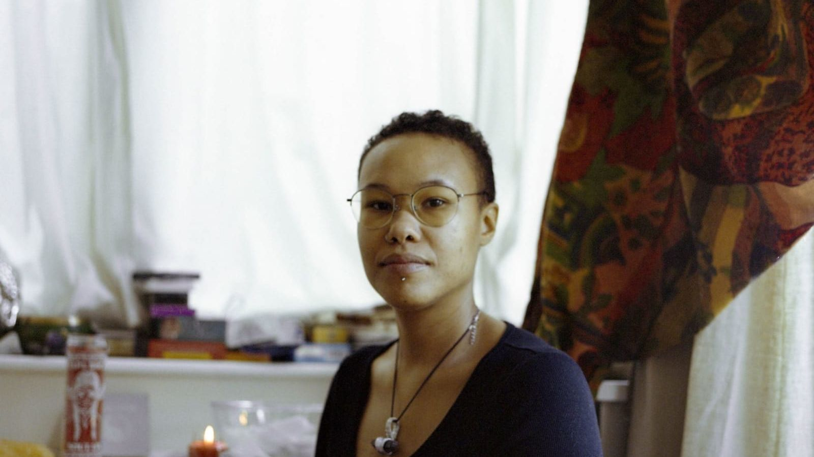 Portrait of a black woman called 'Corinna' taken in her home by Harriet Moore.