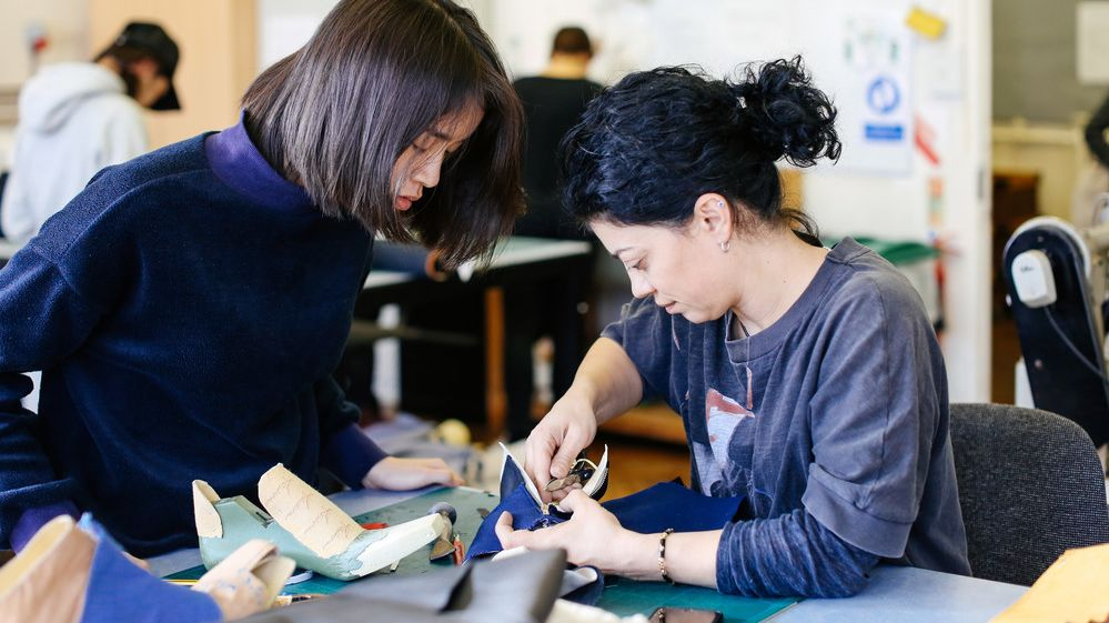 Two asian female students in a workshop leaning over a piece of work with tools in hand
