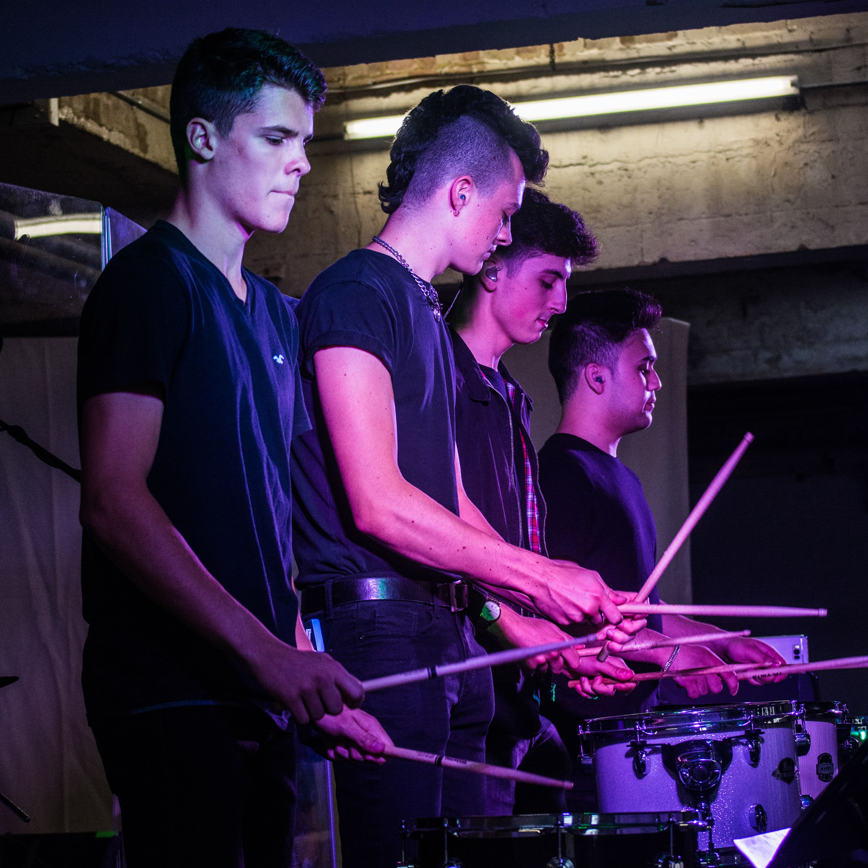 Students playing the drums during a live performance