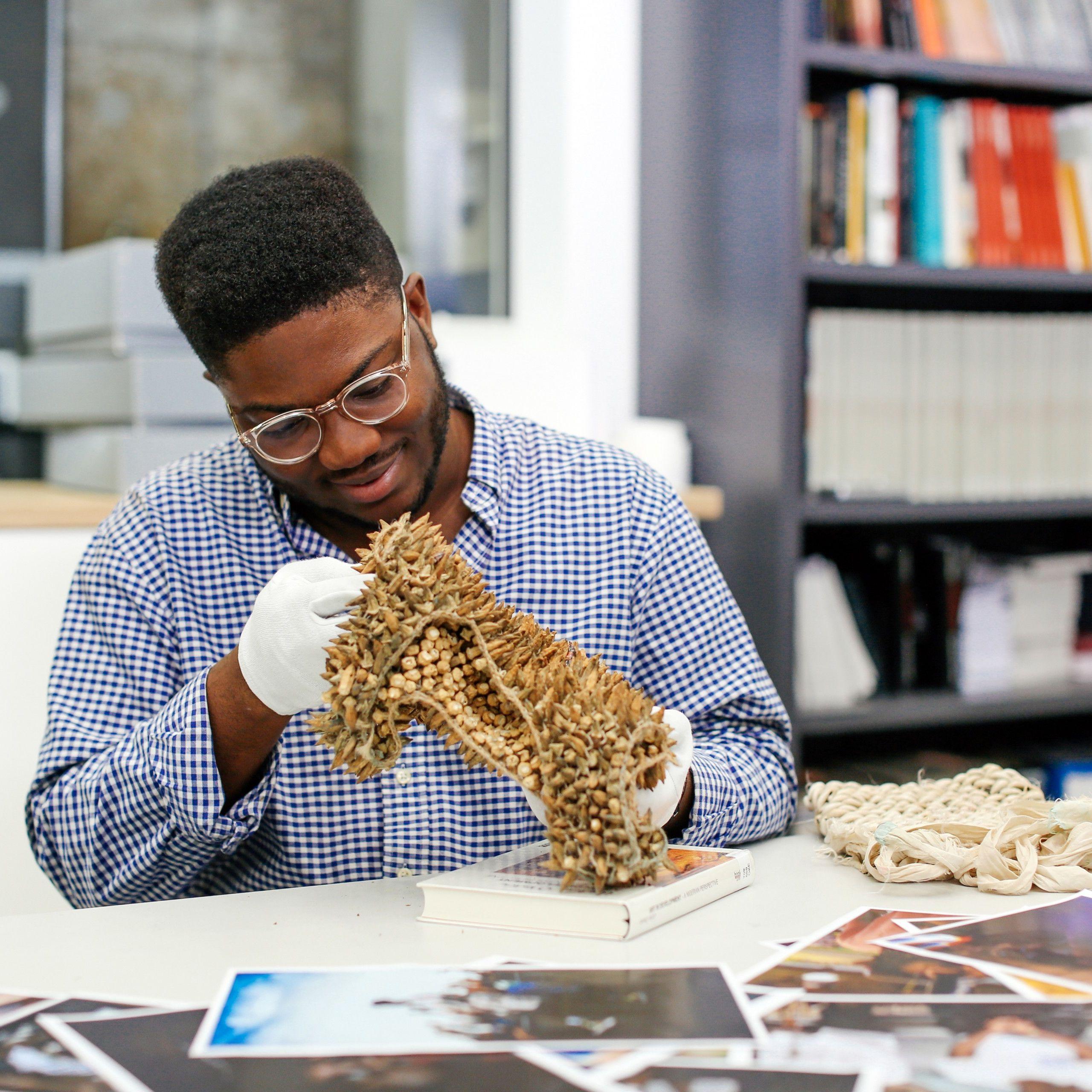 Student creating a sculpture at a desk