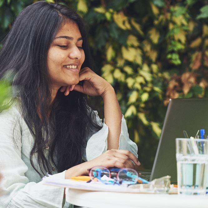Student working on laptop in garden