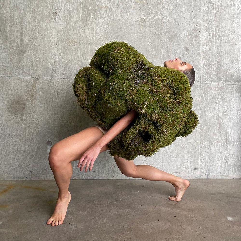 Figure bend back wearing large mossy garment