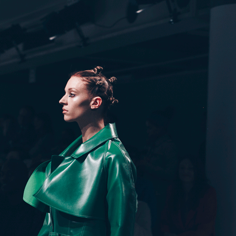 Model with hair in bunches and wearing a Marta Jakubowski coat, on the catwalk