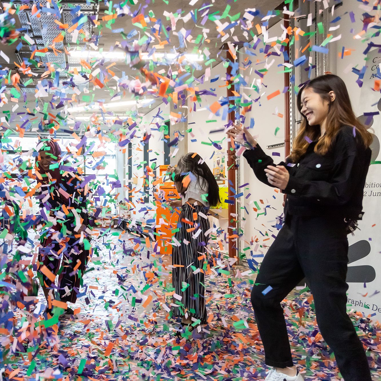 Four students throw green, orange, purple and white confetti at each other at the BA Graphic Design Summer Show at Camberwell