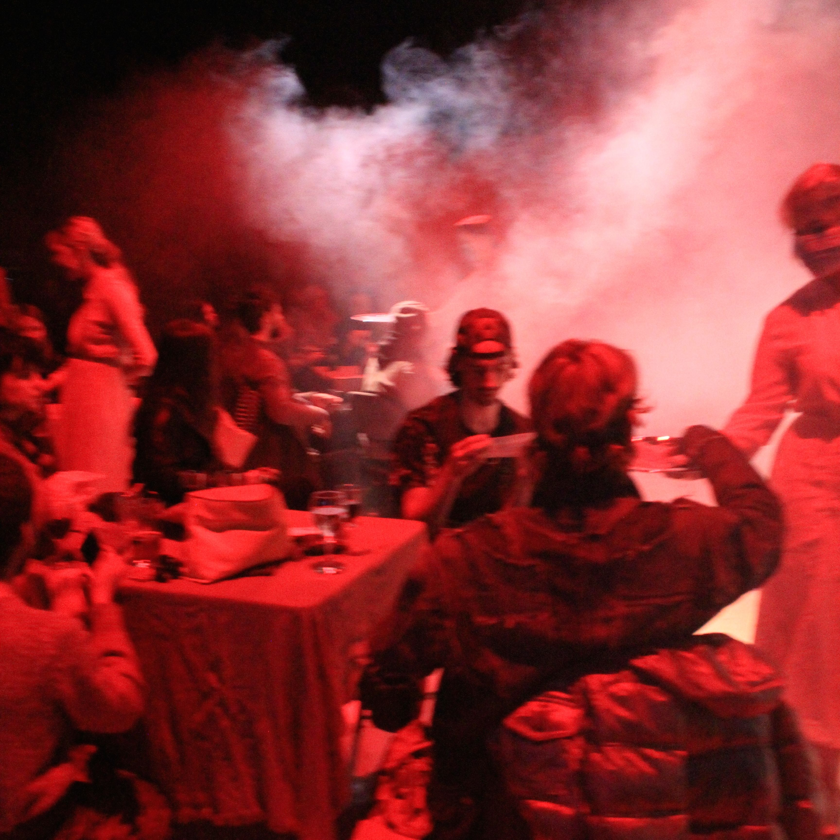 People sittign and standing in a red-lit room full of dry ice