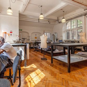 Student at sewing machine in sewing room at Lime Grove, London College of Fashion