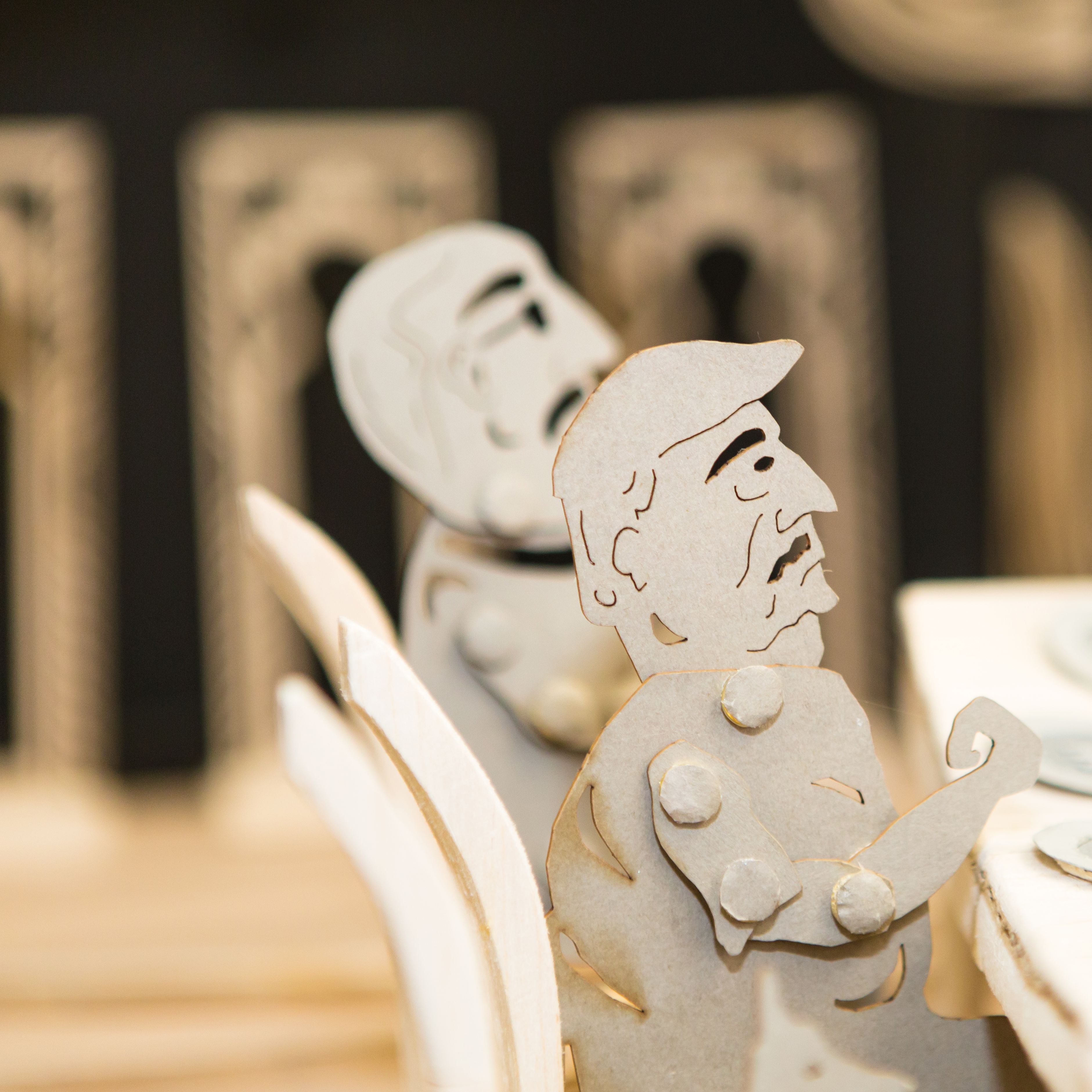 Cardboard characters at a dinner table - part of BA Live Events and Television course project