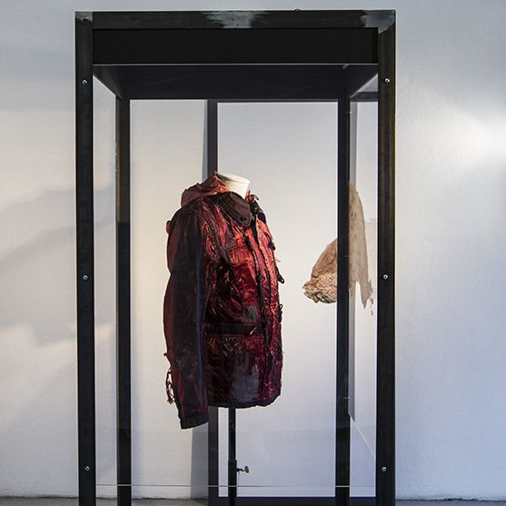 a red and black jacket suspended in a display case. To the right a window revealing a street. To the left (behind the display case) a framed photography of the same jacket.