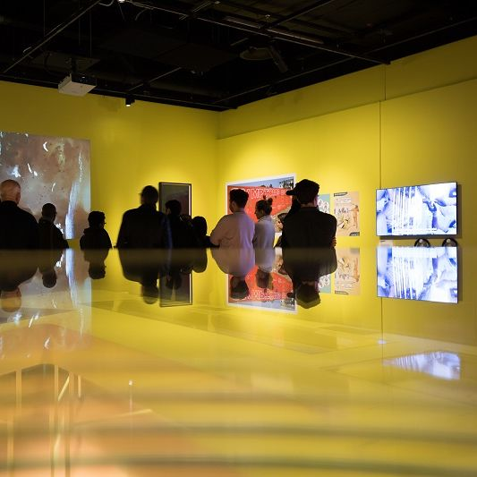 Photo of a group of people looking at a collection of paintings displayed on a yellow wall