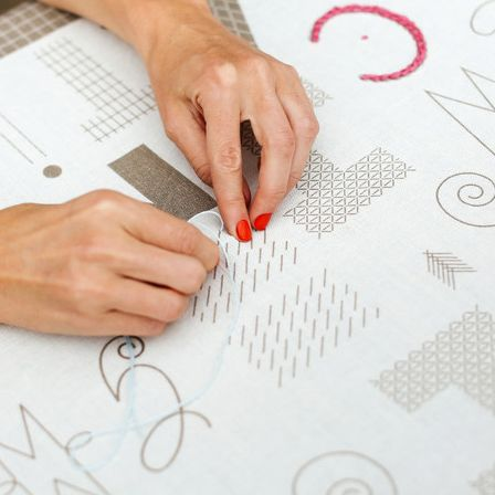 Woman embroidering text onto paper