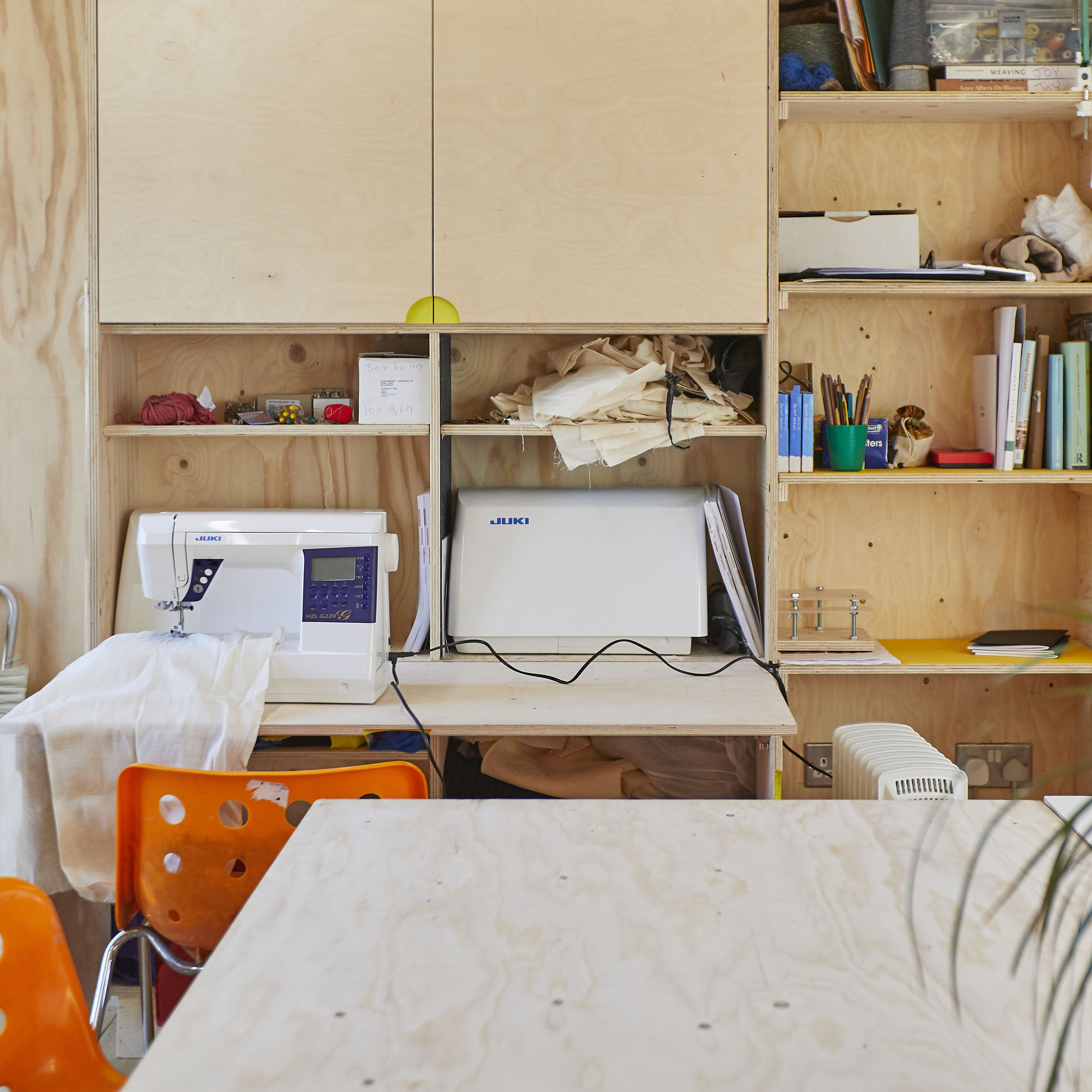 A informal but well organised workshop with plywood walls and cupboards, orange chairs, a sewing machine and a tabletop in the foreground