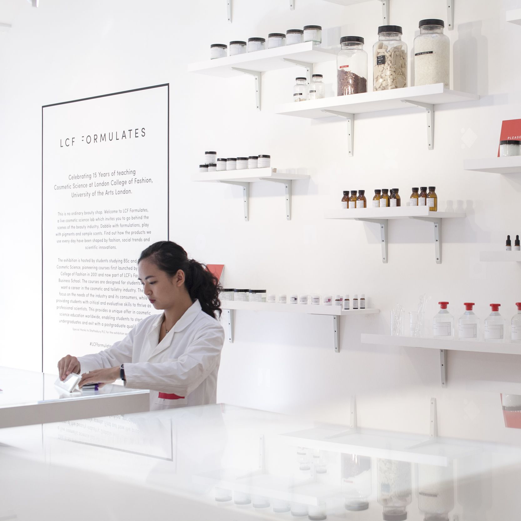Woman in white lab coat with shelves of cosmetics behind her. LCF Formulates Cosmetic Science exhibition, Fashion Business School Summit, Kingly Court. Copyright holder: Emmi Hyyppa