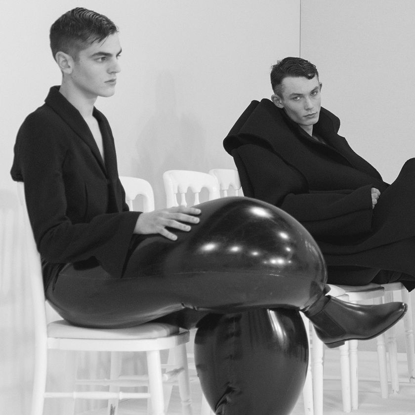 Four male models seated in loose black clothing