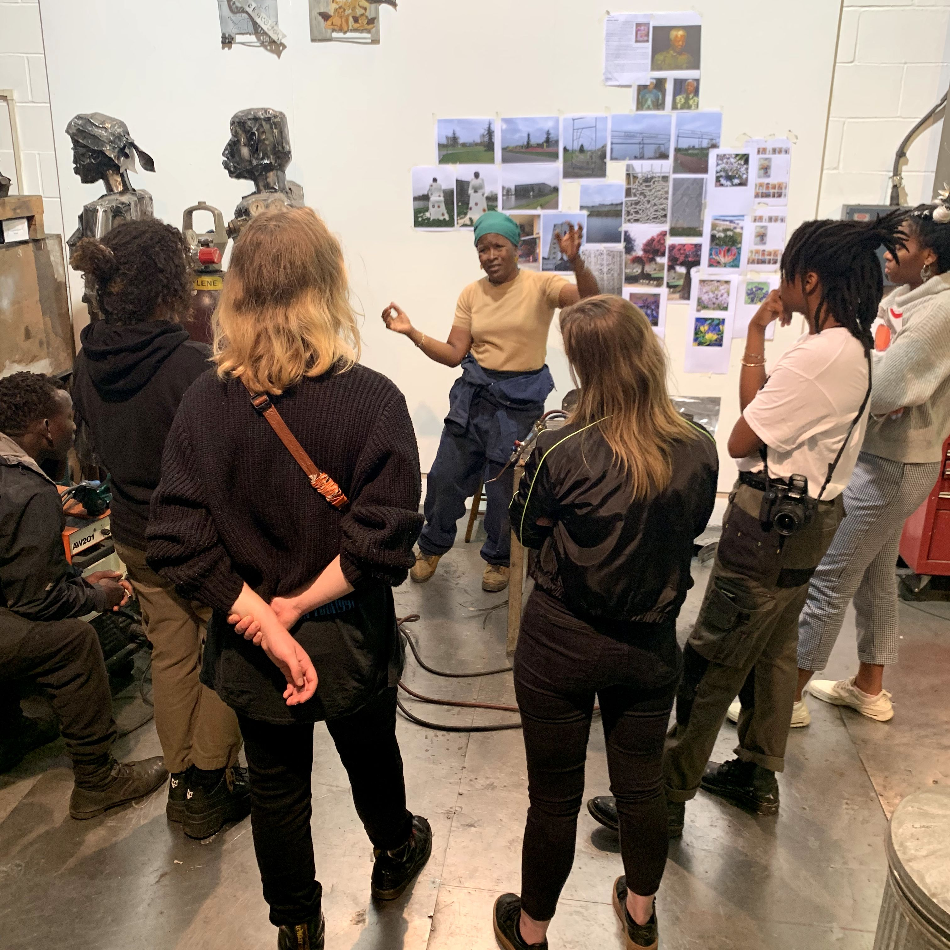 A group of students inside the artist Sokari Douglas Camp's studio which is full of photographs and sculptures