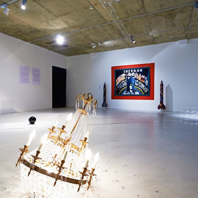 A curated collection in a gallery with a shattered but lit chandelier on the floor.