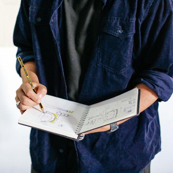 Man drawing in a sketchbook. BA (Hons) Design Management, Sketchbook by Jessy Heikrujam. Copyright holder: Alys Tomlinson