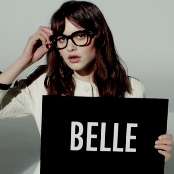 Corinne holding a sign that says 'Belle'