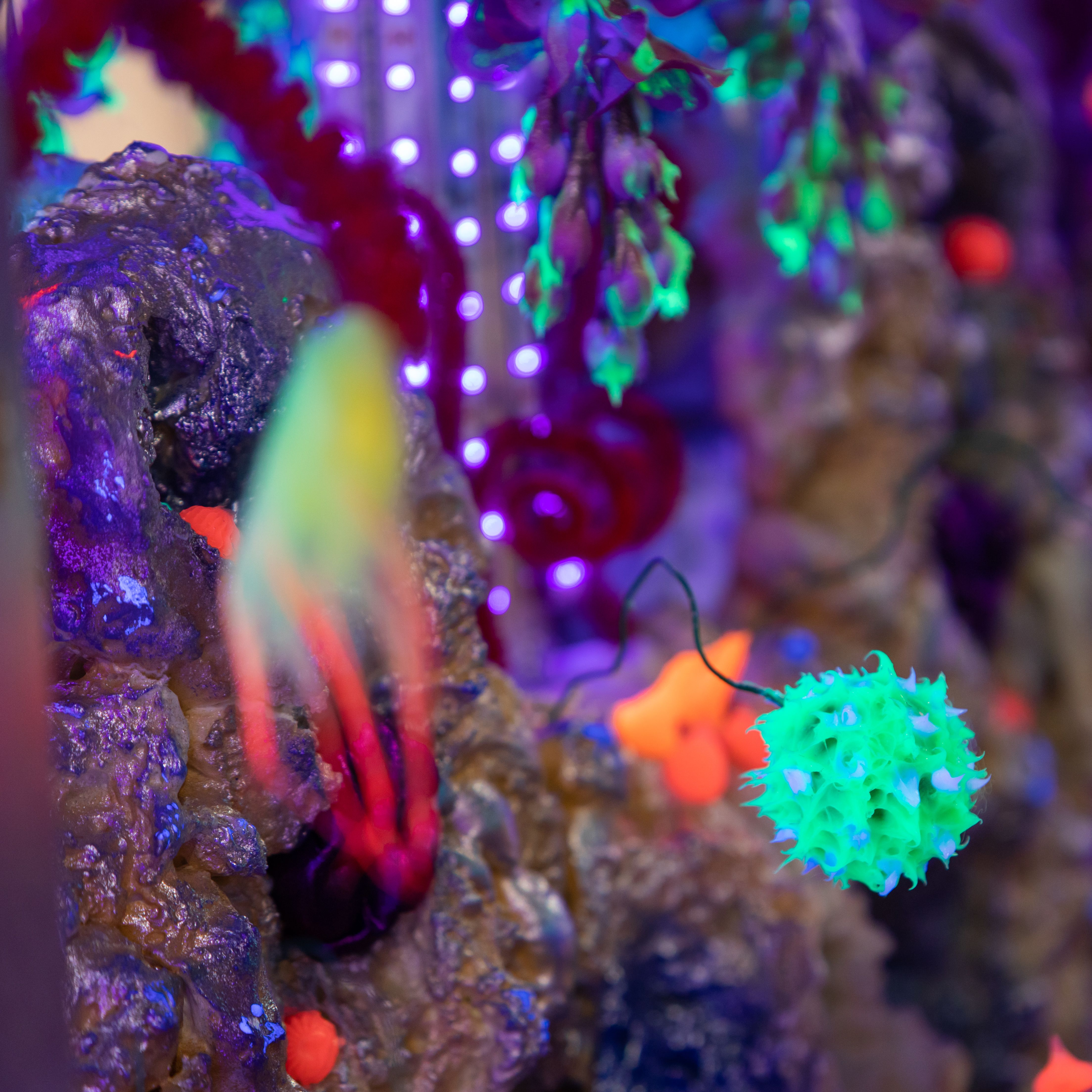 Close up of a colourful installation glowing in the dark