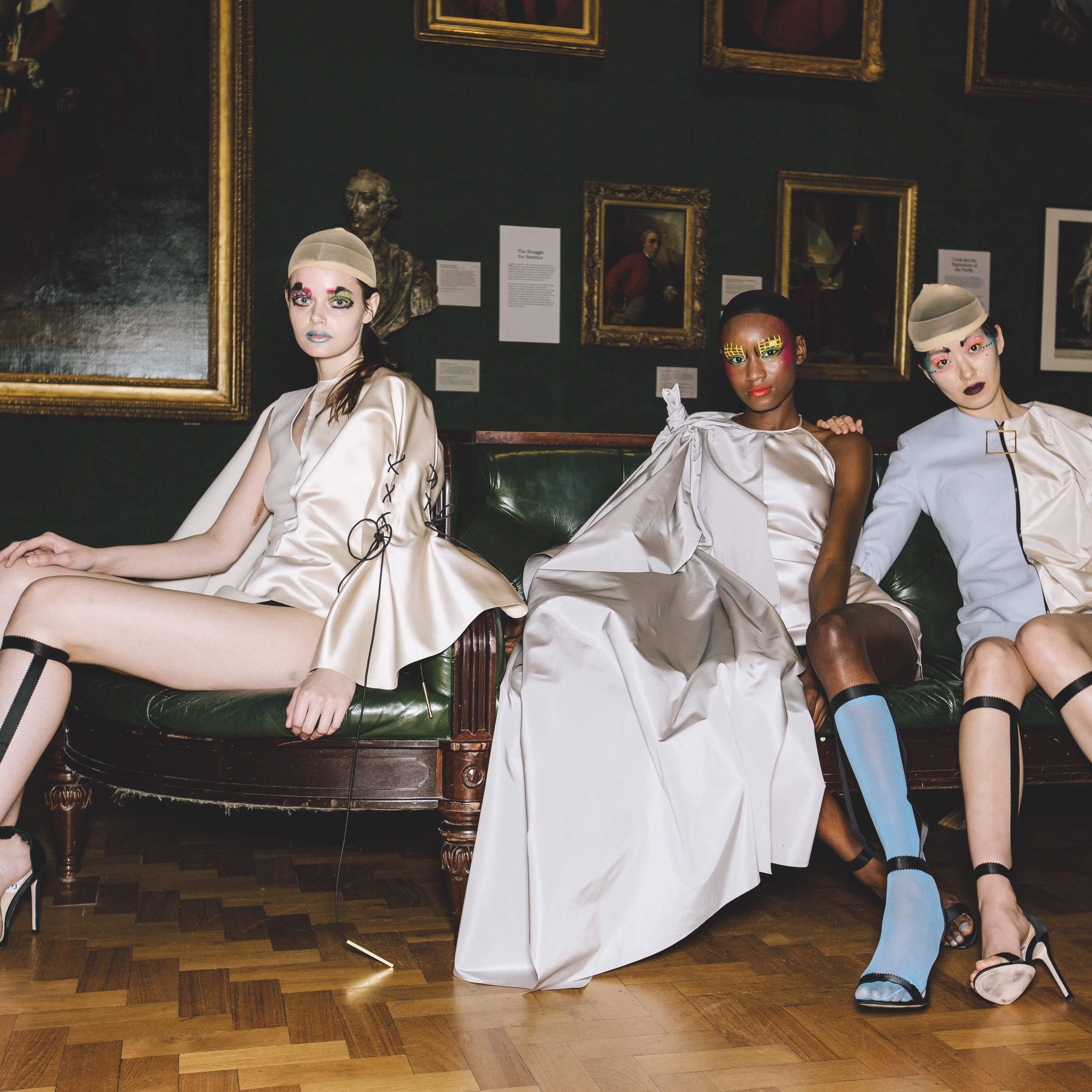 Female models dressed in glossy off white garments, sitting on a sofa at the National Portrait Gallery - by fashion designer Emma Bergamin Davys