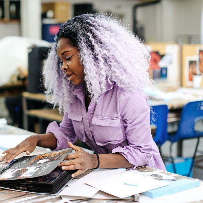 Student with purple hair and purple jumpsuit talks through their portfolio.