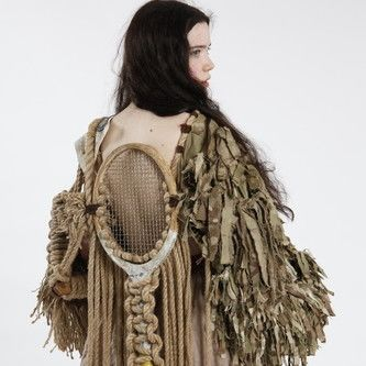 Girl in a large brown garment with lots of texture and big sleeves