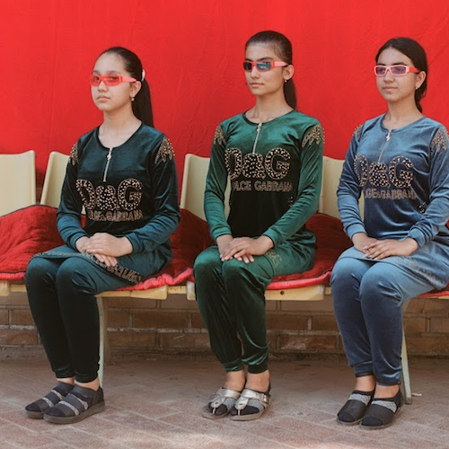 three models with hair pulled back into ponytails sit on chairs draped with red velvety material, all wearing red sunglasses and dolce & gabbana print garments.