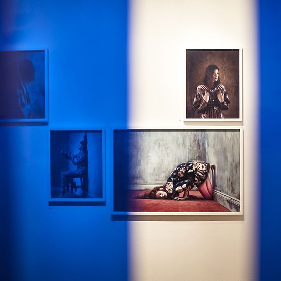 six framed images on exhibition wall, filtered through blue PVC overlay, with middle segment in full colour. Framed images of models in different poses. In focus - images of models falling over, sitting propped against a wall, in multicoloured garments.