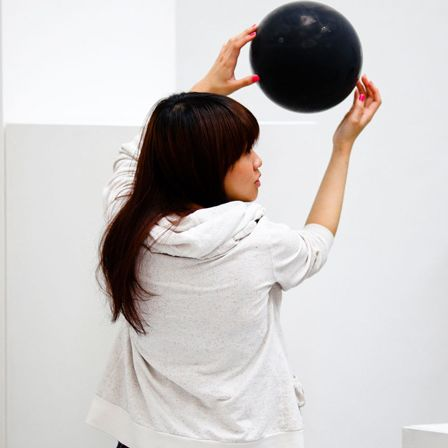 Woman holding a black ball against white wall