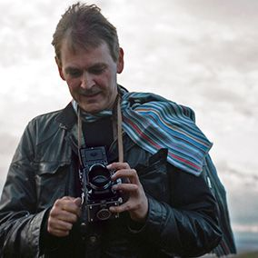A picture of a man standing outside holding a vintage camera.