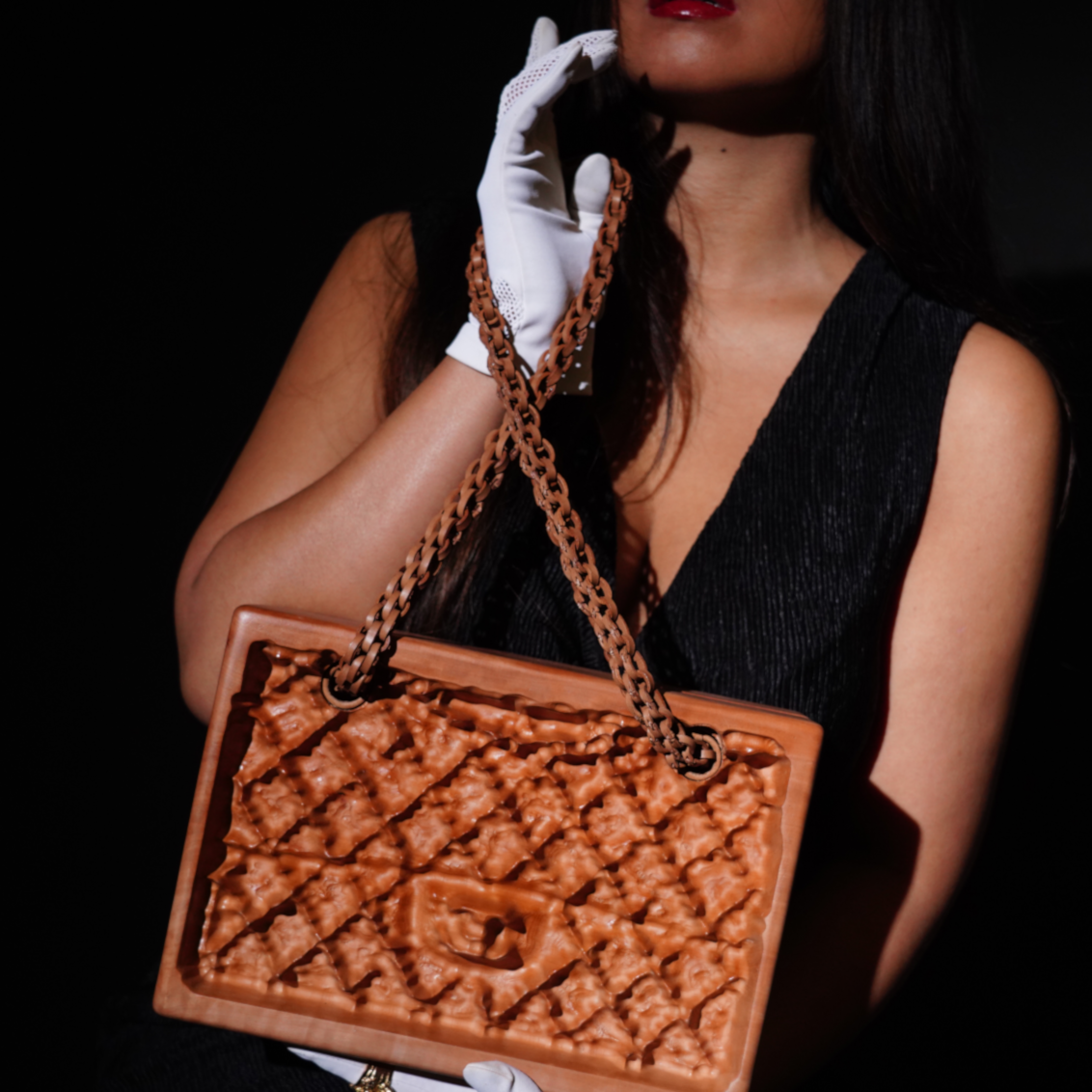 Model showcasing a Chanel handbag made from unique material