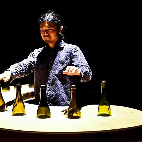 A man interacts with an installation using white bottles submerged in a wooden table.