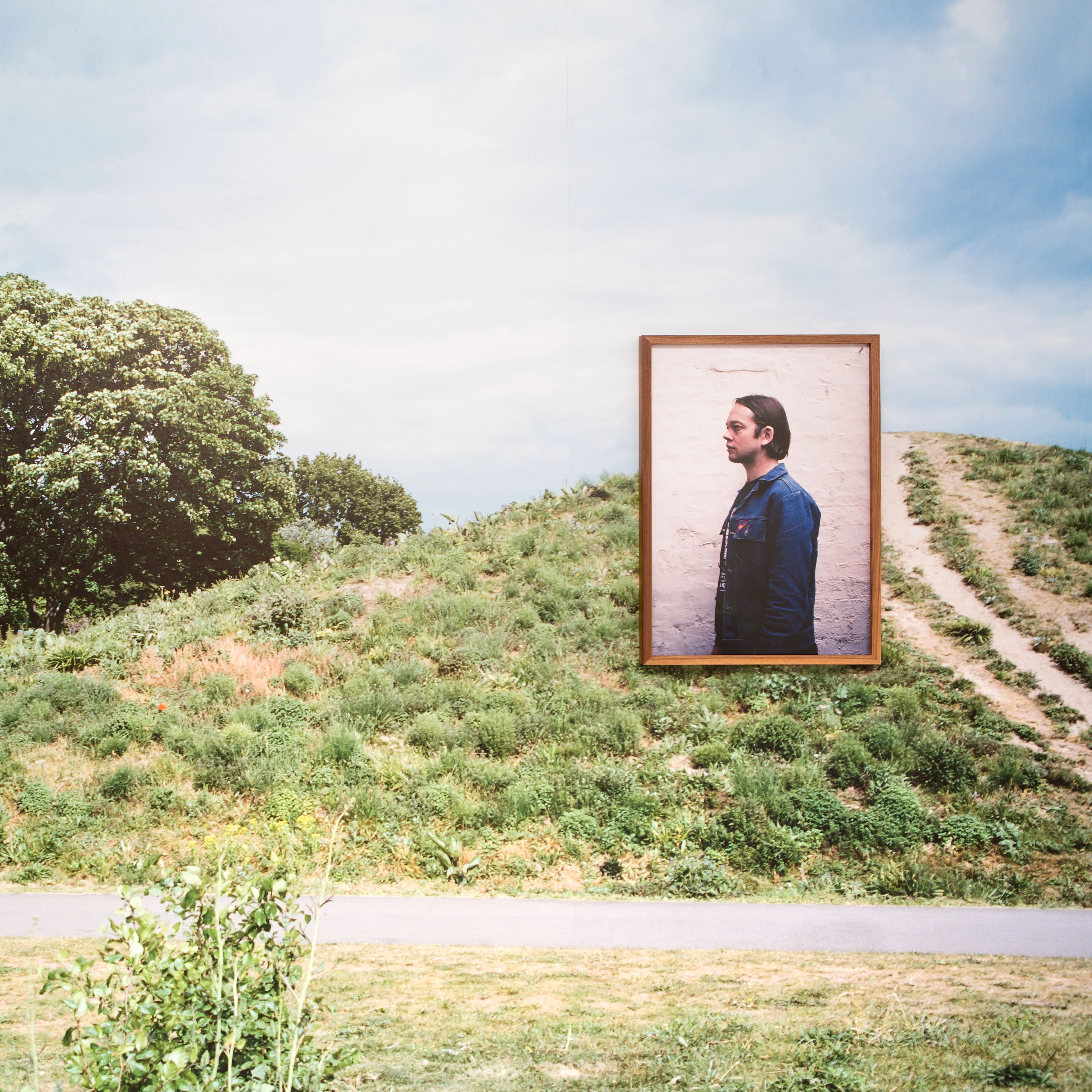 Green space with a large photography installation of a man.
