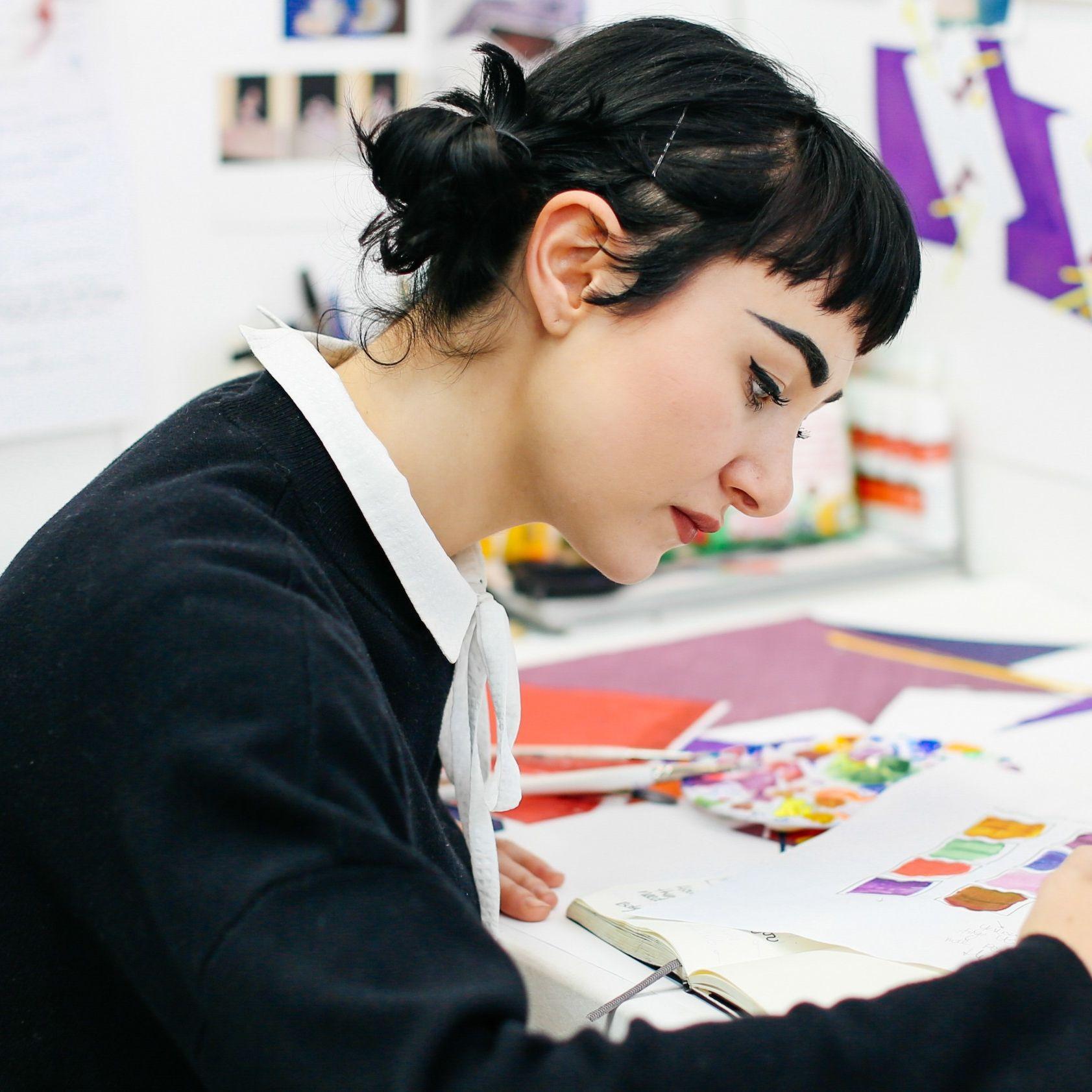 Student at a desk illustrating on a sketchbook