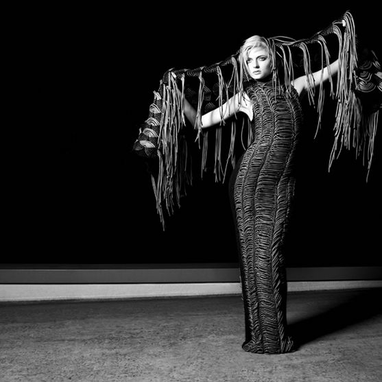 dramatic black and white photo of model posed arms outstretched in front of a black backdrop. Model wears a form fitting maxi tube dress, and a woven fringe garment behind hair and stretched over arms.