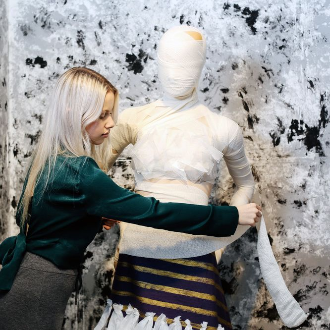 Woman dressing a mannequin, BA Fashion Visual Merchandising and Branding, Tabby Ullah in the studio, Copyright holder: Alys Tomlinson