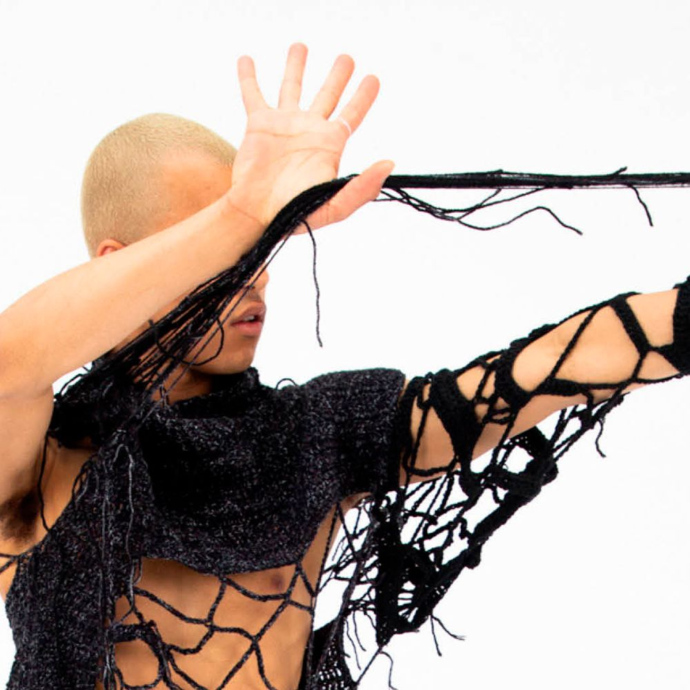 Performer with arm stretched out holding string material