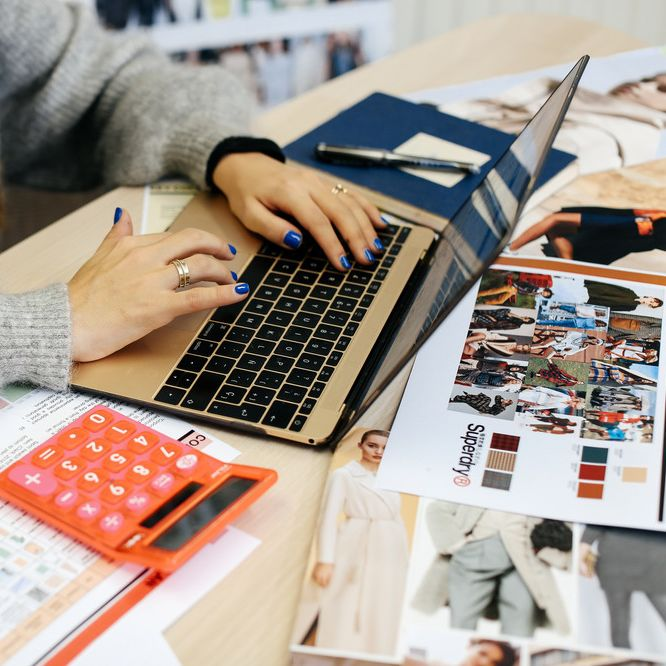 Woman on a laptop with a calculator beside her, MA Fashion: Buying and Merchandising (now PG Cert Fashion: Buying and Merchandising), Zoe Zanon Rives in the studio